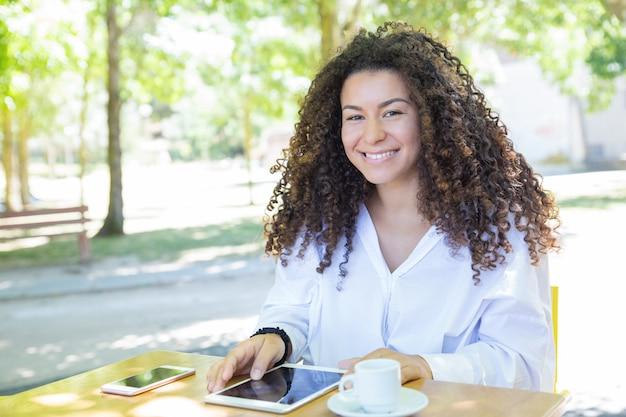 Szczęśliwa dama wyszukuje na pastylka komputerze przy kawiarnia stołem w parku