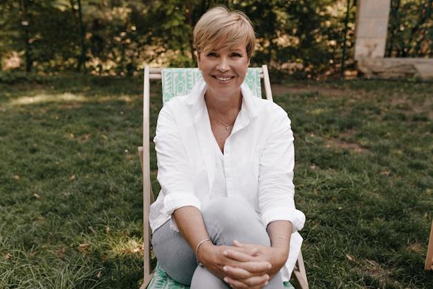 Szczęśliwa dama z nowoczesną blond fryzurą w lekkiej modnej bluzce i spodniach, uśmiechnięta, patrząc w kamerę i siedząca na świeżym powietrzu.