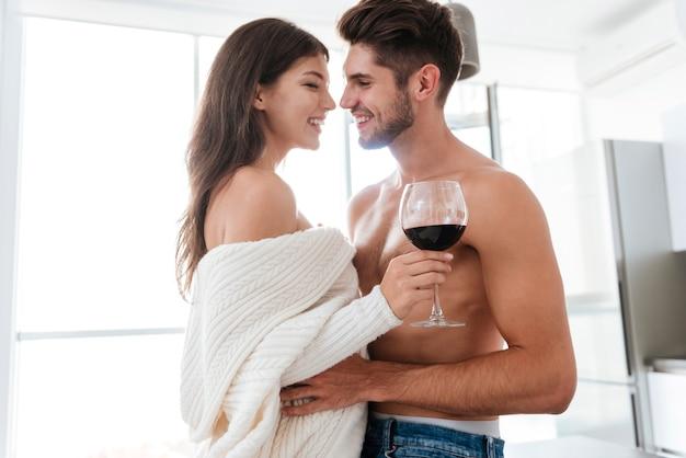 Szczęśliwa delikatna młoda para pije czerwone wino razem w domu