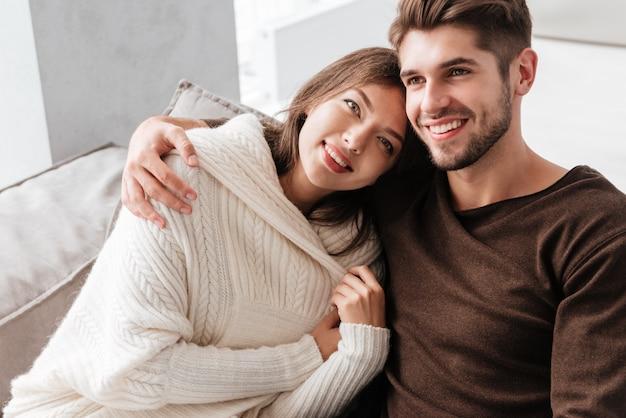 Szczęśliwa delikatna młoda para siedzi i przytula się na kanapie w domu