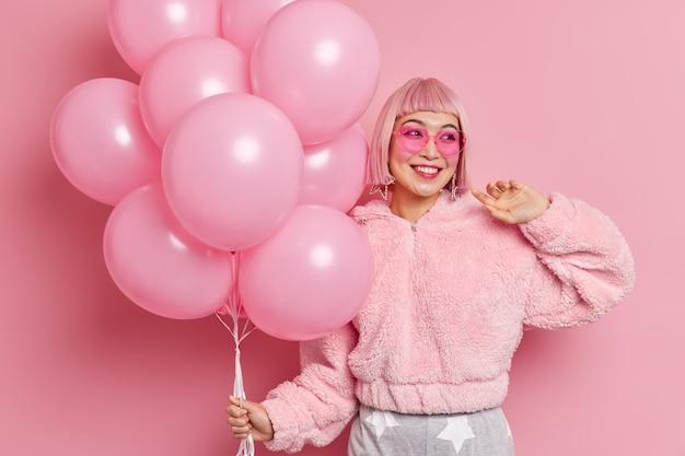 Szczęśliwa, dobrze wyglądająca azjatycka modelka z różowymi włosami, ubrana w zimowe futro, nosi modne okulary przeciwsłoneczne w kształcie serca, trzyma balony, przygotowuje się do świętowania wyjątkowej okazji. koncepcja świątecznej imprezy
