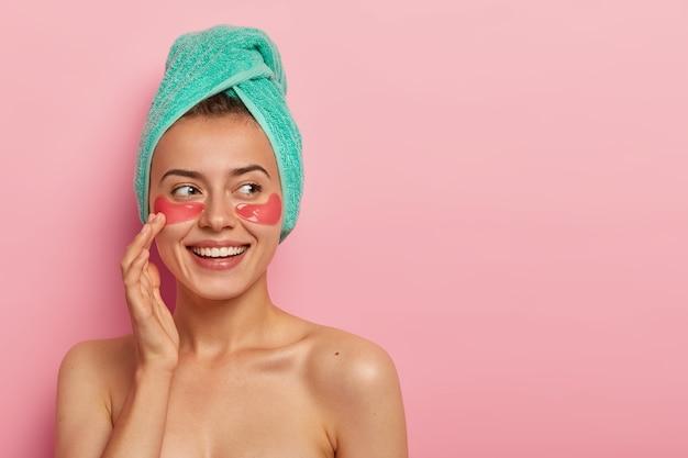 Szczęśliwa, dobrze wyglądająca młoda kobieta delikatnie dotyka twarzy, przyjemnie się uśmiecha, w weekendy spędza wolny czas na zabiegach pielęgnacyjnych, nawilża delikatną skórę pod oczami, dba o ciało i cerę