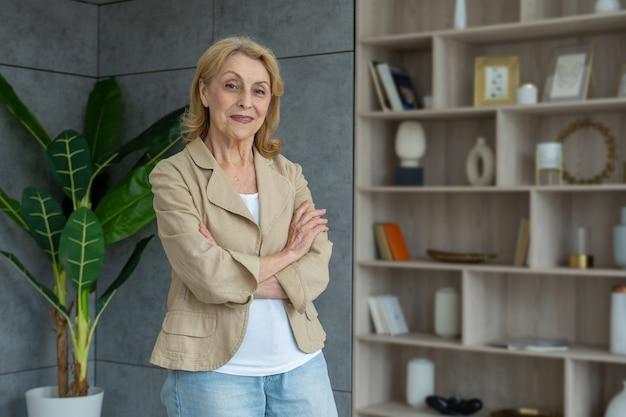 Szczęśliwa dojrzała biznesowa dama stojąca w pokoju starsza w średnim wieku starsza stylowa kobieta
