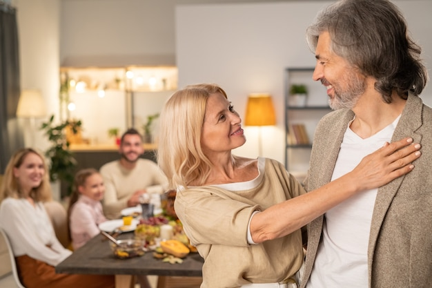 Szczęśliwa dojrzała blond kobieta stojąca obok męża i patrząca na niego na tle młodej pary i ich małej córeczki jedzących świąteczny obiad