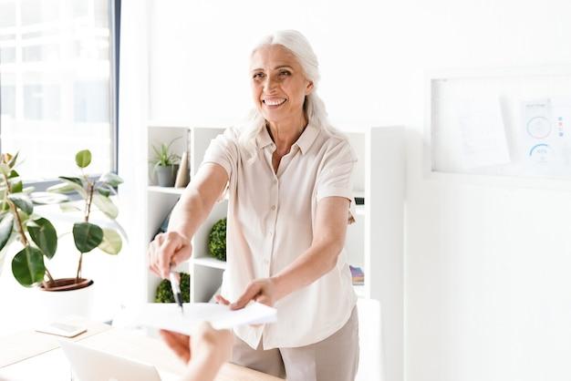 Szczęśliwa dojrzała busienss kobieta daje dokumenty