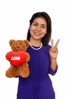 Szczęśliwa dojrzała kobieta azjatyckich trzyma misia z sercem i znakiem miłości odizolowane na białej ścianie