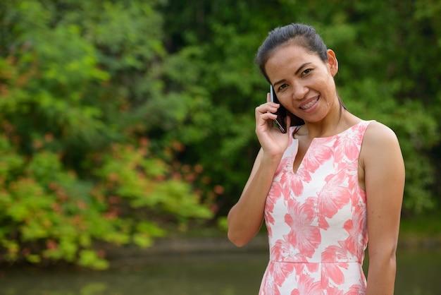 Szczęśliwa dojrzała kobieta azji rozmawia przez telefon w parku na świeżym powietrzu