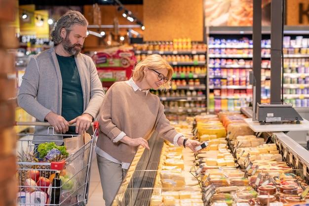 Szczęśliwa dojrzała kobieta bierze zapakowany kawałek sera z wystawy idąc z mężem wzdłuż produktów mlecznych w supermarkecie