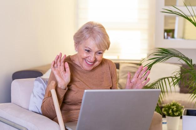 Szczęśliwa dojrzała kobieta macha someone podczas gdy mieć rozmowę wideo nad laptopem w domu. siwowłosa starsza kobieta macha ręką przed laptopem podczas rozmowy wideo z członkami rodziny.
