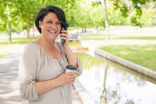 Szczęśliwa dojrzała kobieta opowiada na telefonie komórkowym