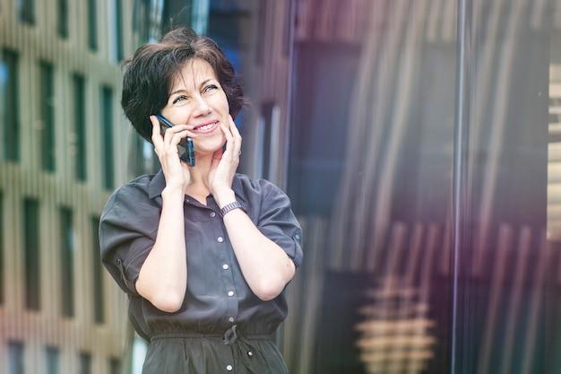 Szczęśliwa dojrzała kobieta rozmawia telefon i uśmiecha się