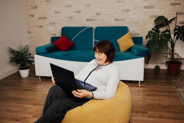 Szczęśliwa dojrzała kobieta siedzi na żółtym fotelu w salonie z laptopem