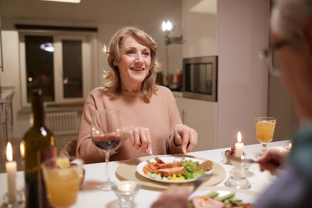 Szczęśliwa dojrzała kobieta siedzi przy stole, je obiad i uśmiecha się do męża podczas ich randki