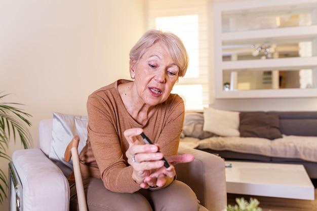 Szczęśliwa dojrzała kobieta sprawdza poziom cukru we krwi z glukometrem w domu. kobieta testuje na wysoki poziom cukru we krwi. kobieta trzyma urządzenia do pomiaru cukru we krwi