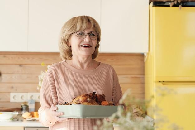 Szczęśliwa dojrzała kobieta trzyma danie z indykiem w okularach i uśmiecha się