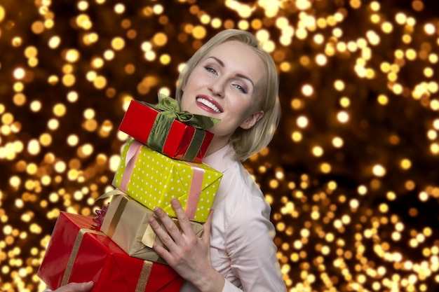 Szczęśliwa dojrzała kobieta trzyma stos prezentów