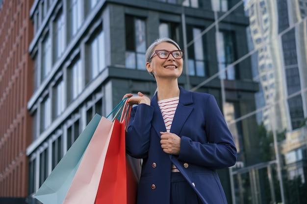 Szczęśliwa dojrzała kobieta trzyma torby na zakupy