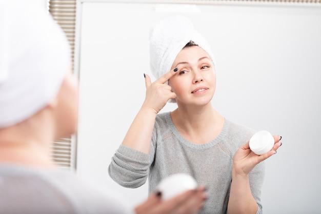 Szczęśliwa dojrzała kobieta używa kosmetyczną śmietankę chować zmarszczki.