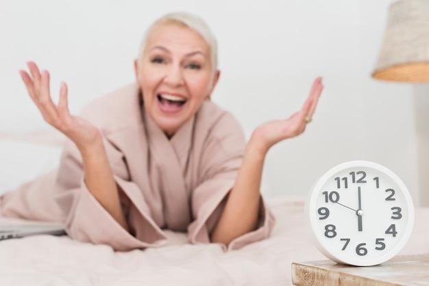 Szczęśliwa dojrzała kobieta w bathrobe pozuje z zegarem
