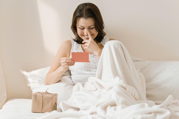 Szczęśliwa dojrzała kobieta w domu w łóżku z niespodzianka prezenta czytelniczym kartka z pozdrowieniami