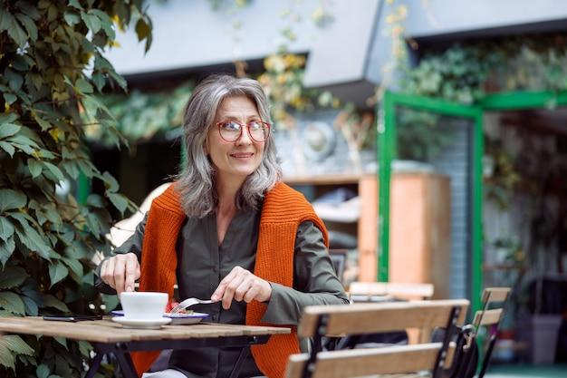 Szczęśliwa dojrzała kobieta w okularach je deser siedząc przy małym stoliku na zewnątrz