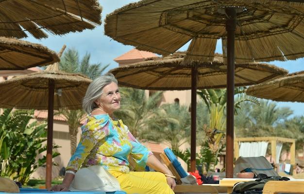Szczęśliwa dojrzała kobieta w pobliżu basenu na wakacjach