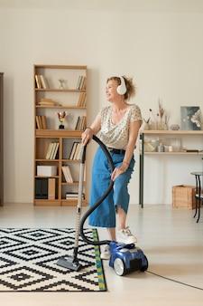 Szczęśliwa dojrzała kobieta w stroju domowym używa odkurzacza, sprzątając salon i śpiewając w słuchawkach do swojej ulubionej muzyki