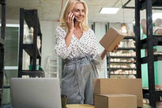Szczęśliwa dojrzała kobieta właściciel małej firmy uśmiecha się rozmawiając przez telefon trzymając karton, podczas gdy
