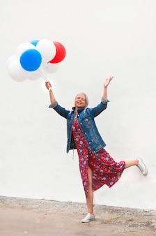 Szczęśliwa dojrzała kobieta z białymi, czerwonymi i niebieskimi balonami na tle białej ściany