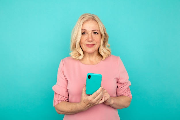 Szczęśliwa dojrzała kobieta z telefonem komórkowym odizolowywającym na niebieskim tle.