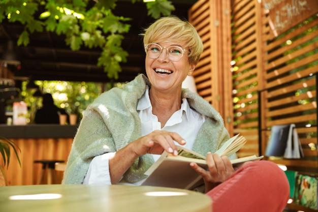 Szczęśliwa dojrzała kobieta zawijająca w koc czyta książkę