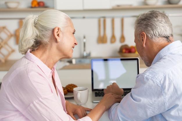 Szczęśliwa dojrzała kochająca pary rodzina przy kuchennym używa laptopem
