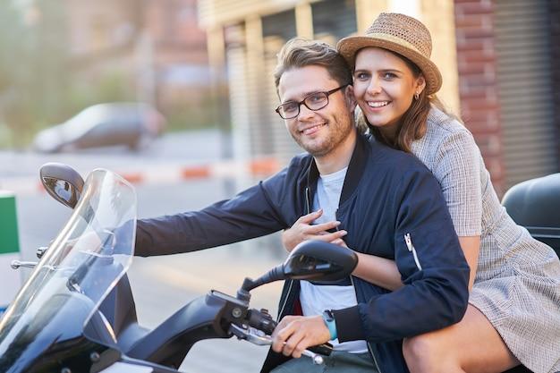 Szczęśliwa dojrzała para jedzie na hulajnodze po mieście w słoneczny dzień