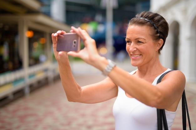 Szczęśliwa dojrzała piękna turystka kobieta robi zdjęcie z telefonem na ulicach miasta na zewnątrz