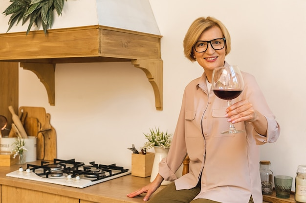 Szczęśliwa dojrzała starsza starsza blondynka w kuchni do picia czerwonego wina. trzymając kieliszek z winem.
