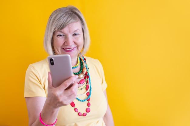 Szczęśliwa dojrzała starsza starsza pani kobieta rozmawia telefon komórkowy w stylowych ubraniach