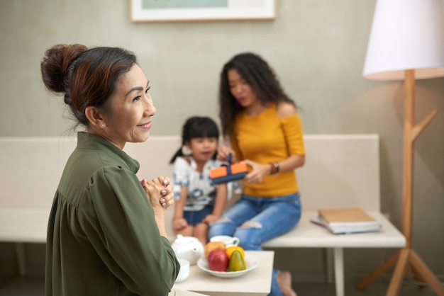 Szczęśliwa dojrzała wietnamka trzymająca się za ręce i patrząca na bok, ciesząc się czasem z rodziną w domu