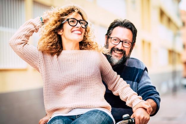 Szczęśliwa dorosła dojrzała piękna para ciesz się i baw się razem jeżdżąc na rowerze - mężczyzna niosący kobietę i dużo się śmiejąc - szczęśliwi aktywni ludzie w czasie wolnym - portret w średnim wieku i okulary