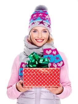 Szczęśliwa dorosła kobieta daje prezent na boże narodzenie w zimowej odzieży wierzchniej na białym
