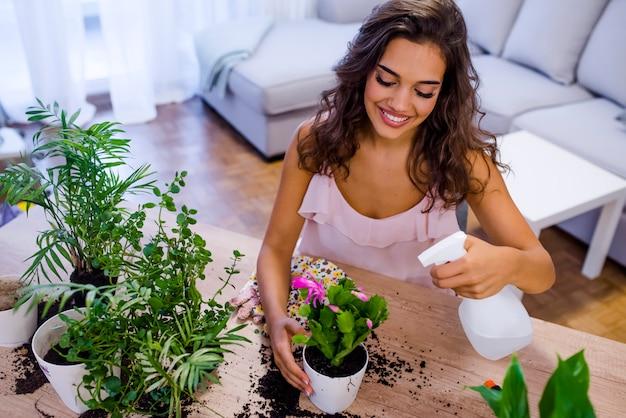 Szczęśliwa dorosła kobieta nawadnia domowej rośliny opuszcza salowego