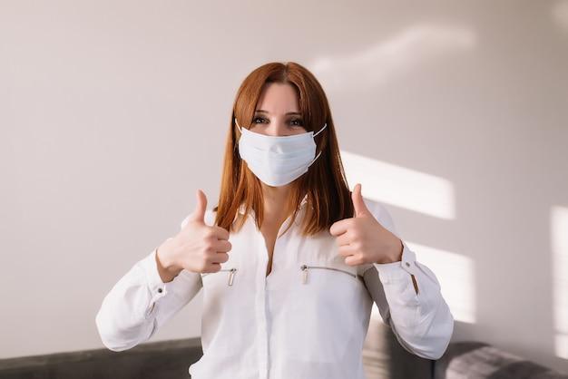 Szczęśliwa dorosła kobieta nosi maskę ochronną, na białym tle na szarym tle. pandemia wirusa koronawirusa - covid-19. reklama maski medycznej