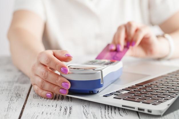Szczęśliwa dorosła kobieta siedzi w domu na leżance z laptopem i kartą kredytową. płacenie rachunków i zamówień. koncepcja zakupów online i e-commerce.