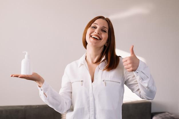 Szczęśliwa dorosła kobieta trzyma alkoholu gel lub mydła mydła przeciwbakteryjnego myjni. pojęcie higieny.