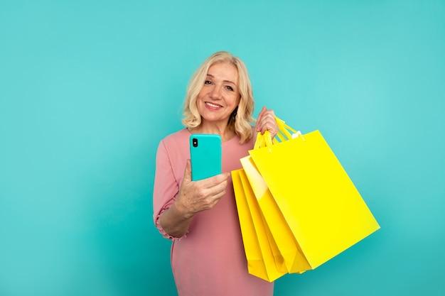 Szczęśliwa dorosła kobieta trzyma telefon i żółte torby.