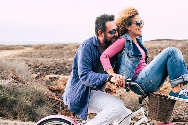Szczęśliwa dorosła para kaukaska bawiąca się rowerem w aktywnym wypoczynku na świeżym powietrzu