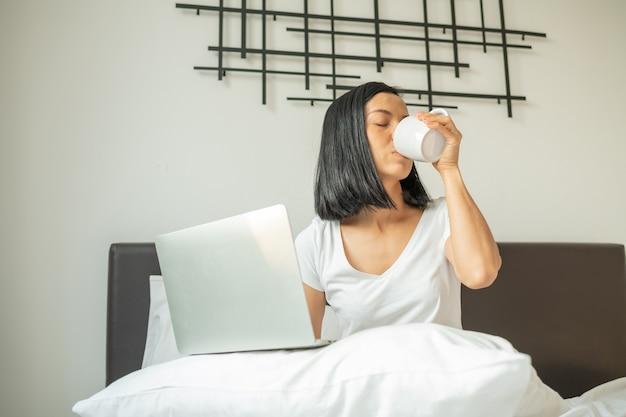 Szczęśliwa dorywczo kobieta pracuje na laptopie siedząc na łóżku w domu.
