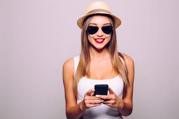 Szczęśliwa dorywczo młoda kobieta za pomocą smartfona na szarej ścianie