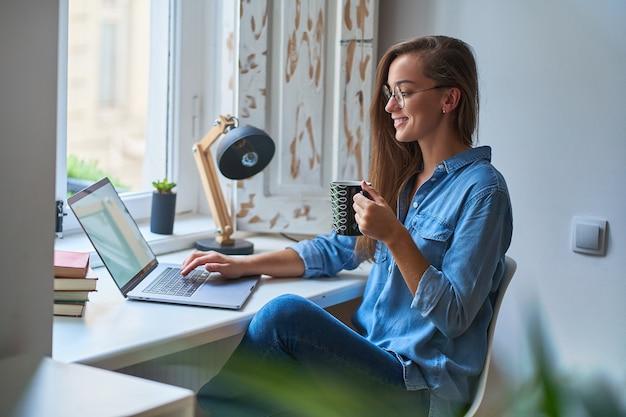 Szczęśliwa dorywczo młoda uśmiechnięta kobieta w okrągłych okularach z filiżanką kawy przeglądająca internet przy komputerze w przytulnym, wygodnym, domowym miejscu pracy przy oknie