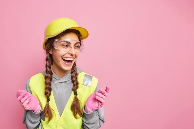 Szczęśliwa doświadczona kobieta inżynier z warkoczami uśmiecha się szczęśliwie rozkłada ręce odwraca wzrok nosi ochronny kask ochronny budowanie munduru pozuje przed różową ścianą z kopią przestrzeni
