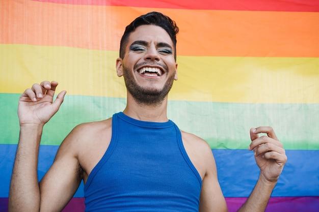 Szczęśliwa drag queen bawi się z tęczową flagą w tle - koncepcja lgbt i transpłciowa - skup się na twarzy